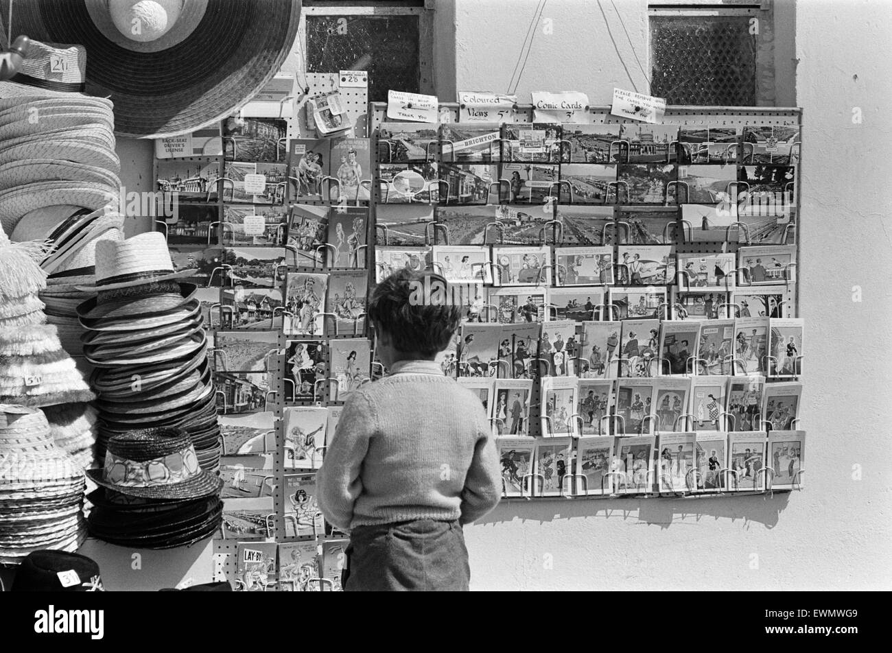 Holiday scenes in Brighton, East Sussex on the Whitsun bank holiday -  a little boy looks at the saucy postcards. - Stock Image