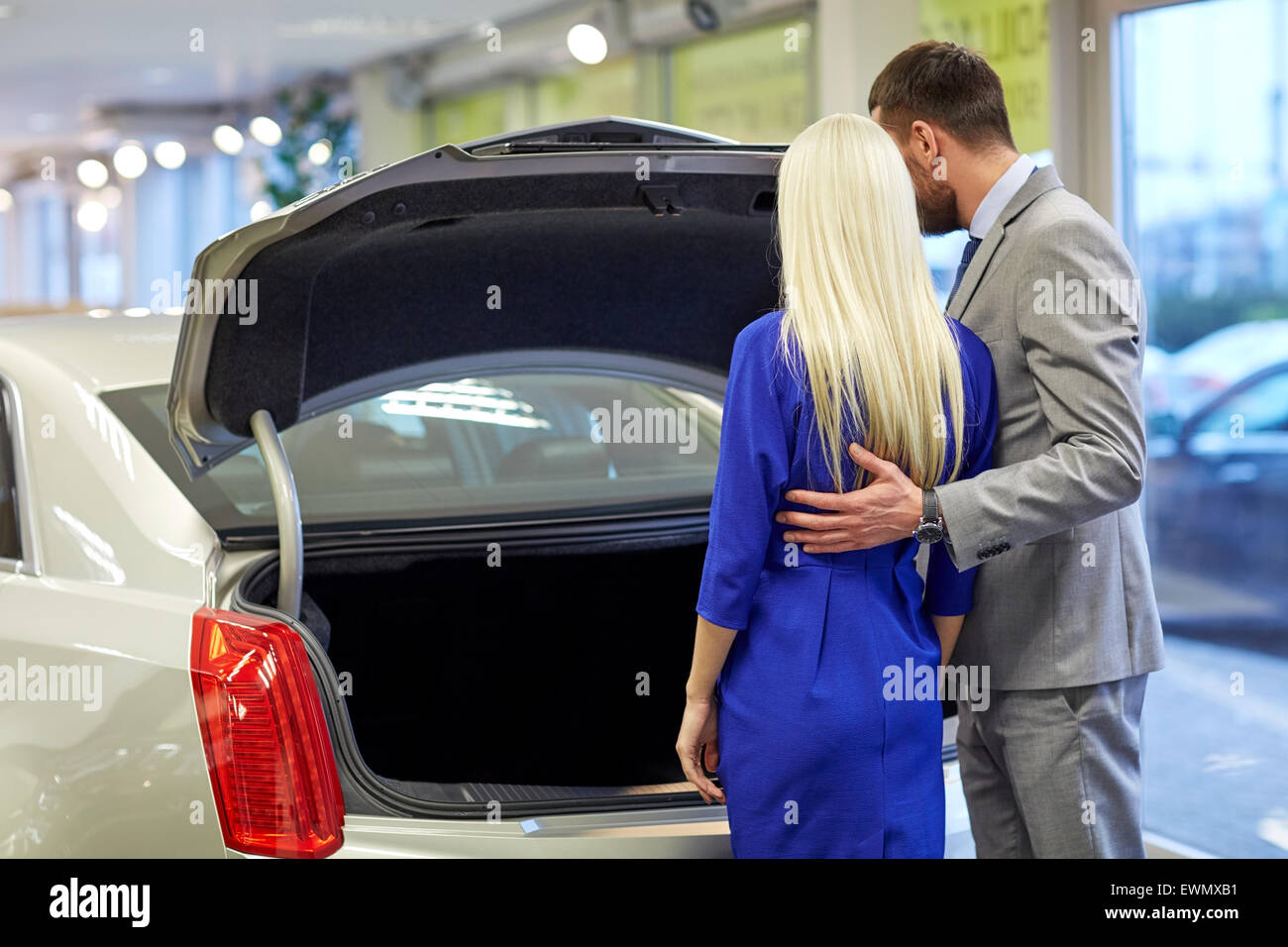 happy couple choosing car in auto show or salon - Stock Image