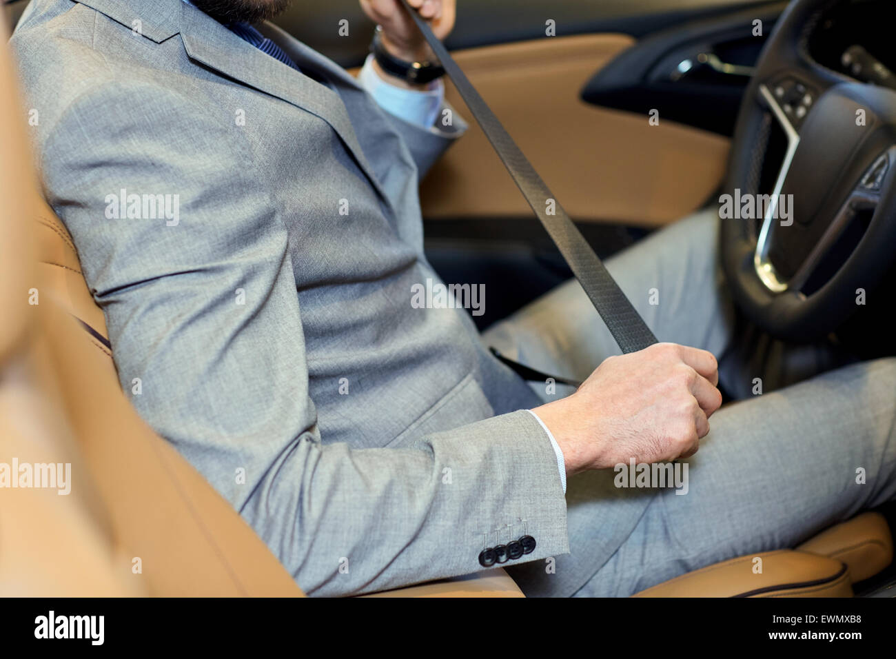 close up of man fastening seat safety belt in car - Stock Image