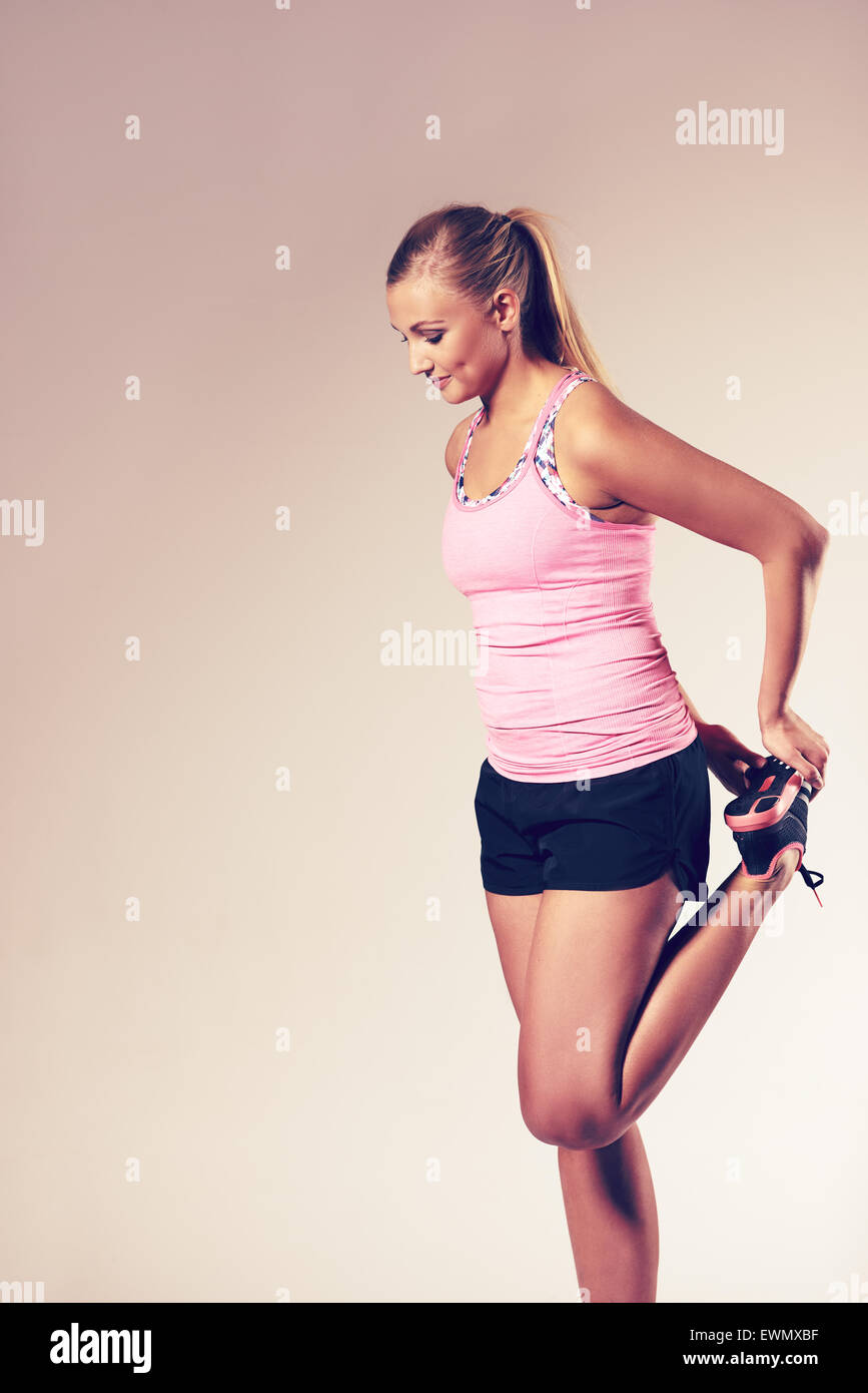 Profile of young woman standing and stretching leg muscles. - Stock Image