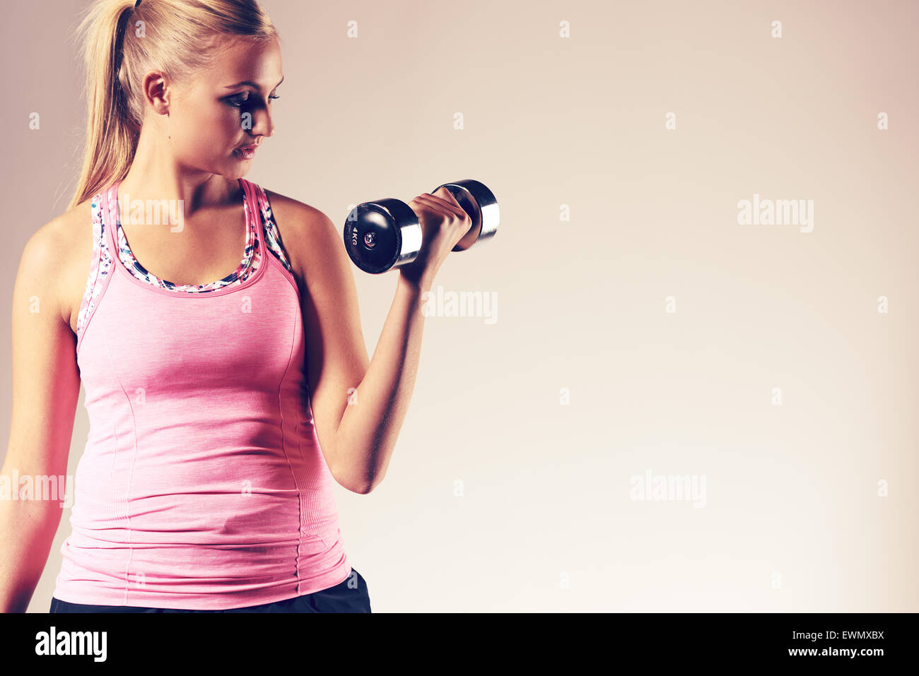 Young woman exercising upper body doing a bicep curl with a free weight. - Stock Image