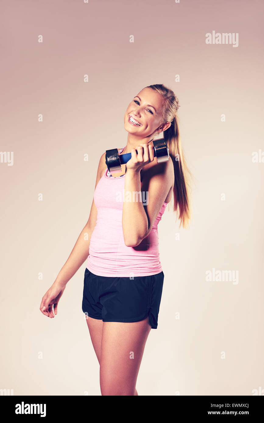 Young woman smiling looking at camera and holding a dumbbell. - Stock Image