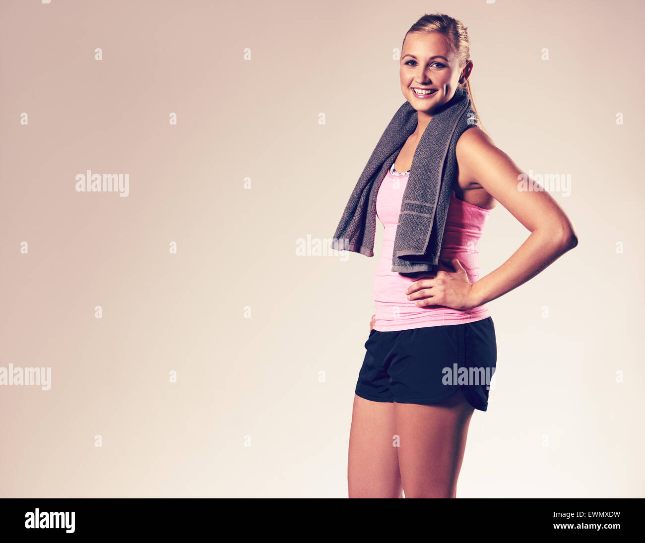 Young woman wearing workout clothes posing with hand on hip and smiling at camera. - Stock Image