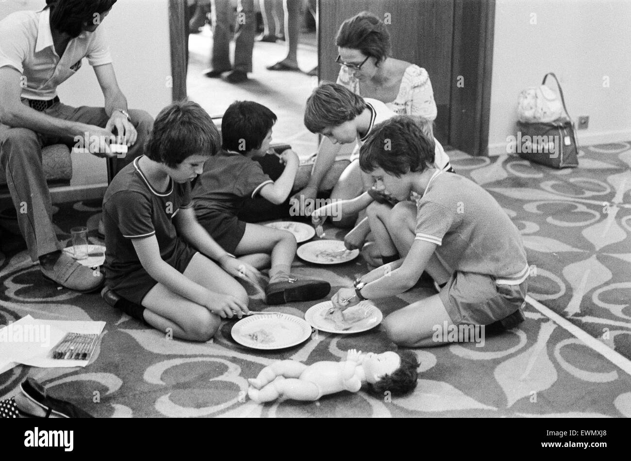 The Turkish invasion of Cyprus. Four boys squat on the floor at the Ledra Palace Hotel to eat a makeshift meal while - Stock Image