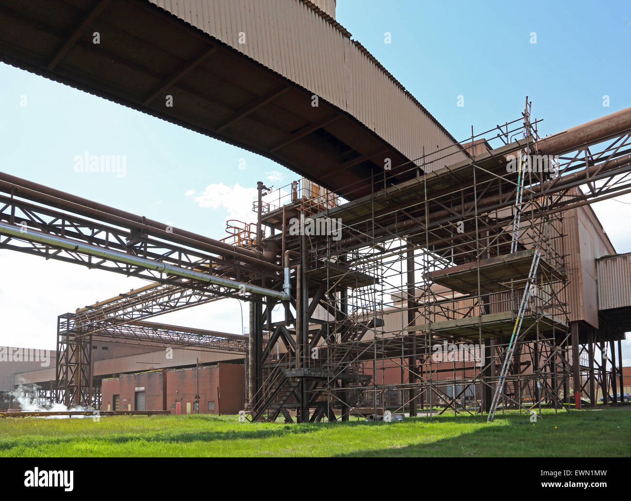 Scaffolding surrounds pipe gantries and conveyor belt housings at the re-opened Redcar Steelworks, Cleveland, UK - Stock Image