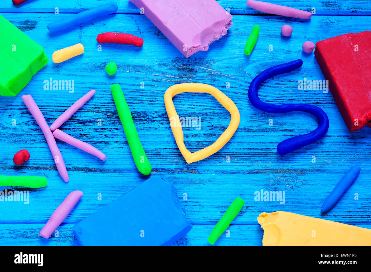 modelling clay of different colors forming the word kids on a blue wooden surface - Stock Image