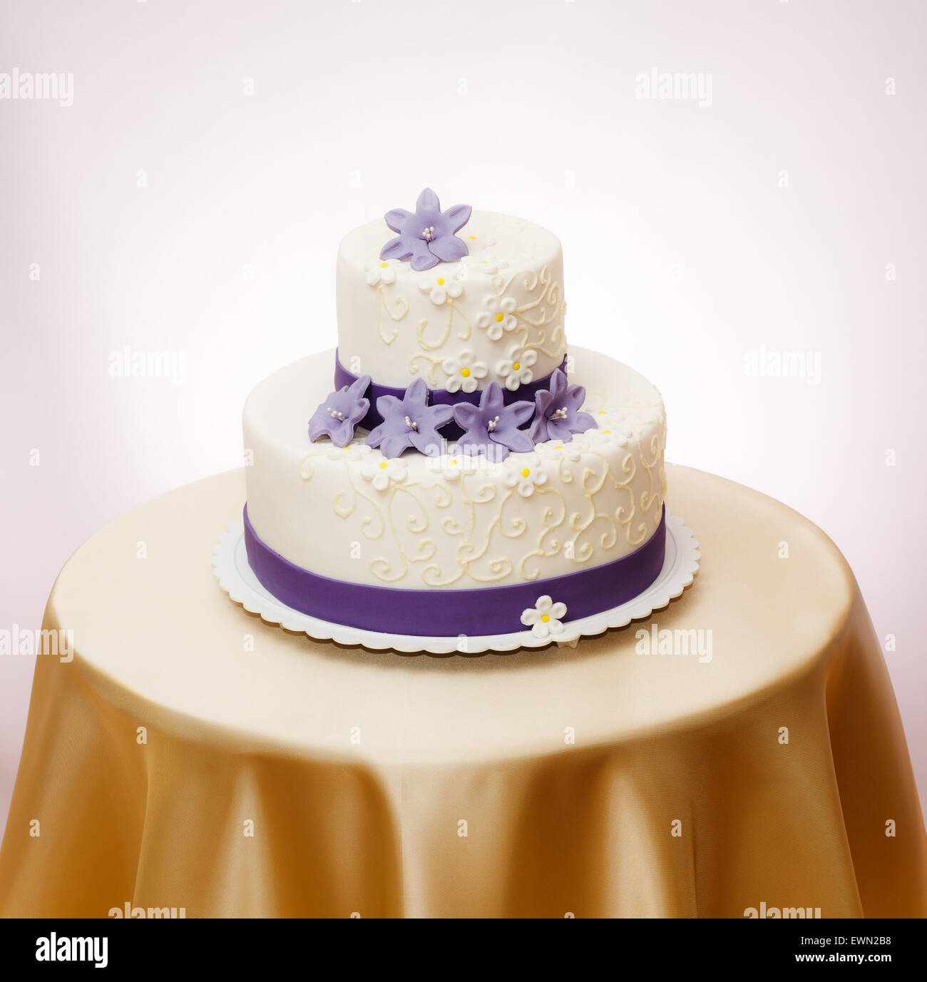 White wedding cake with violet marzipan flower decoration Stock ...