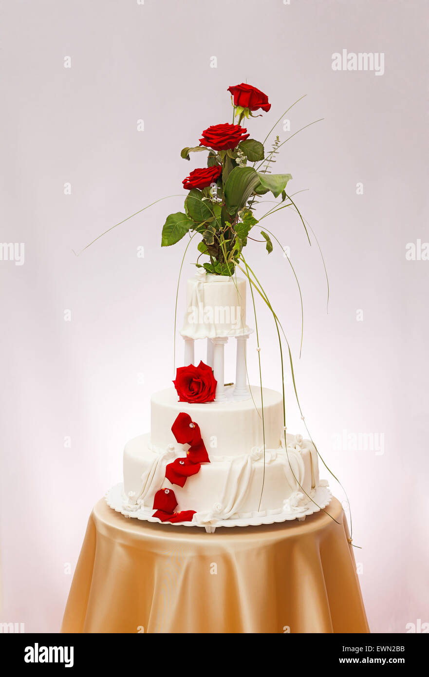 Three-storied white wedding cake with real rose decoration Stock ...