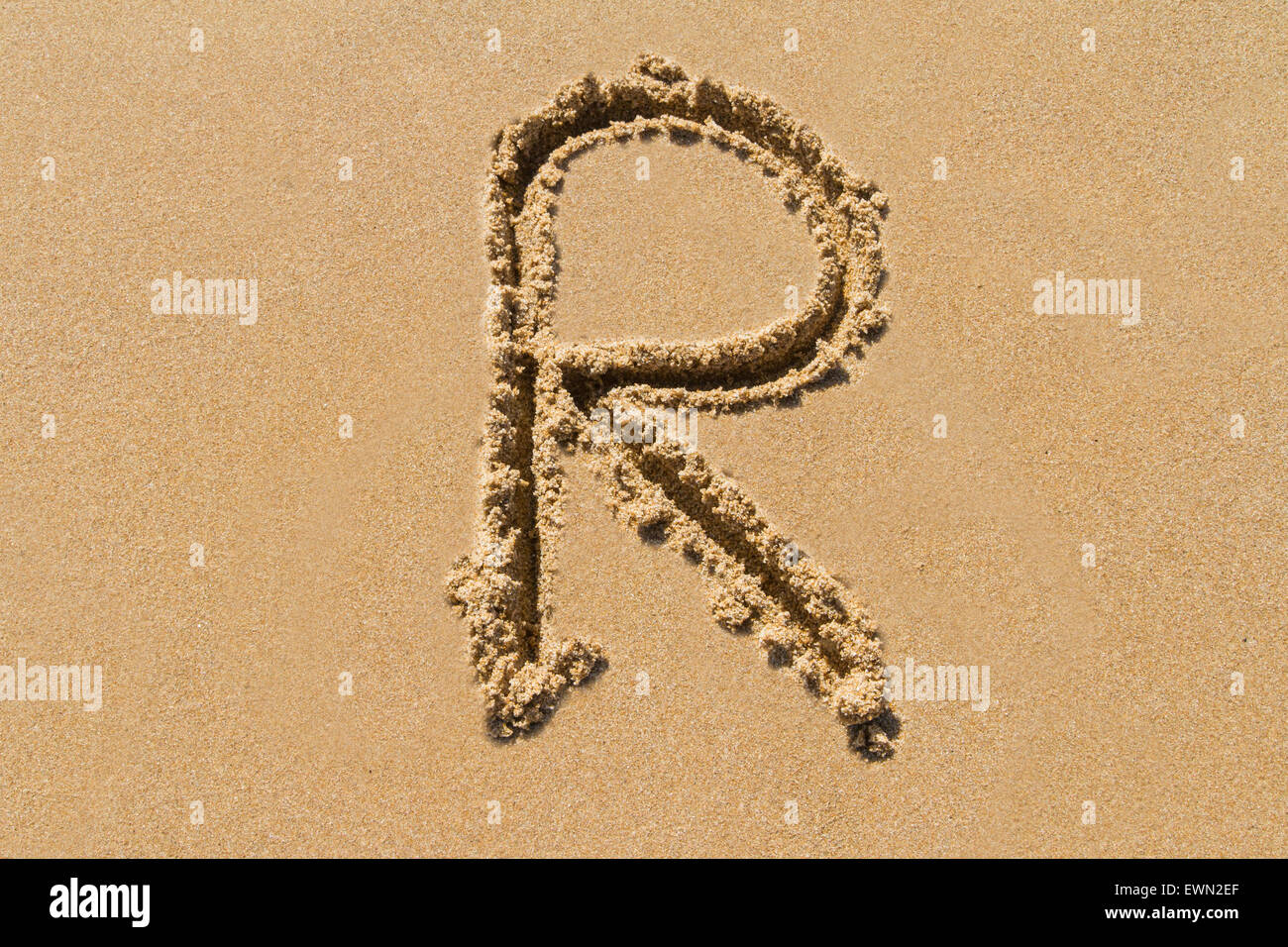 Letter R of the alphabet written on sand with upper case. - Stock Image