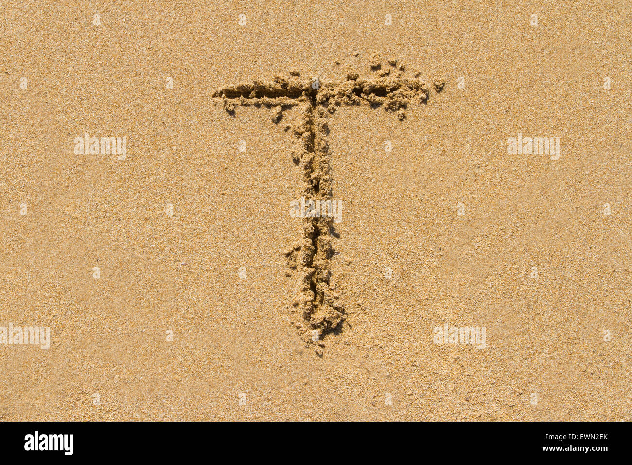 Letter T of the alphabet written on sand with upper case. - Stock Image