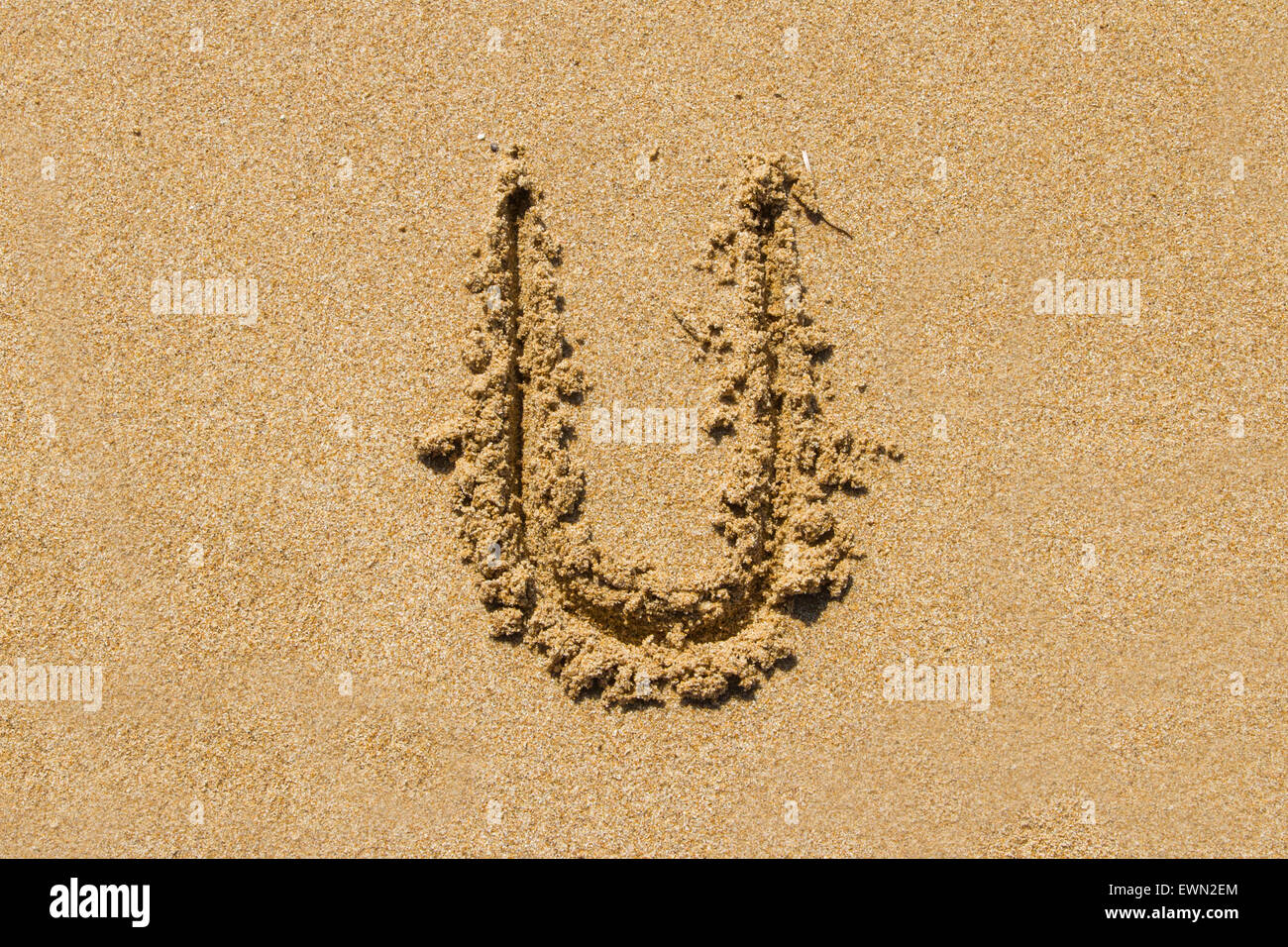 Letter U of the alphabet written on sand with upper case. - Stock Image