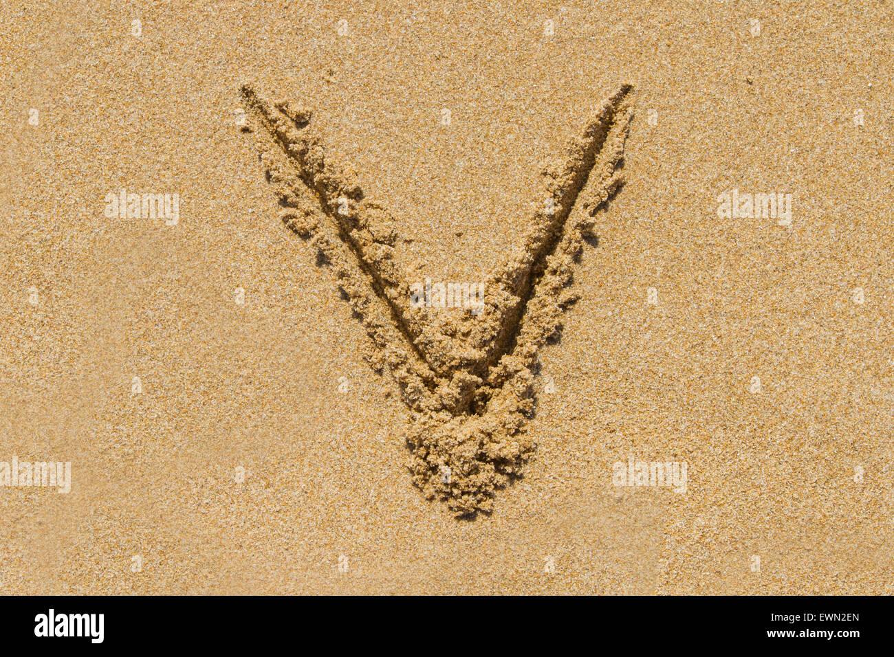 Letter V of the alphabet written on sand with upper case. - Stock Image