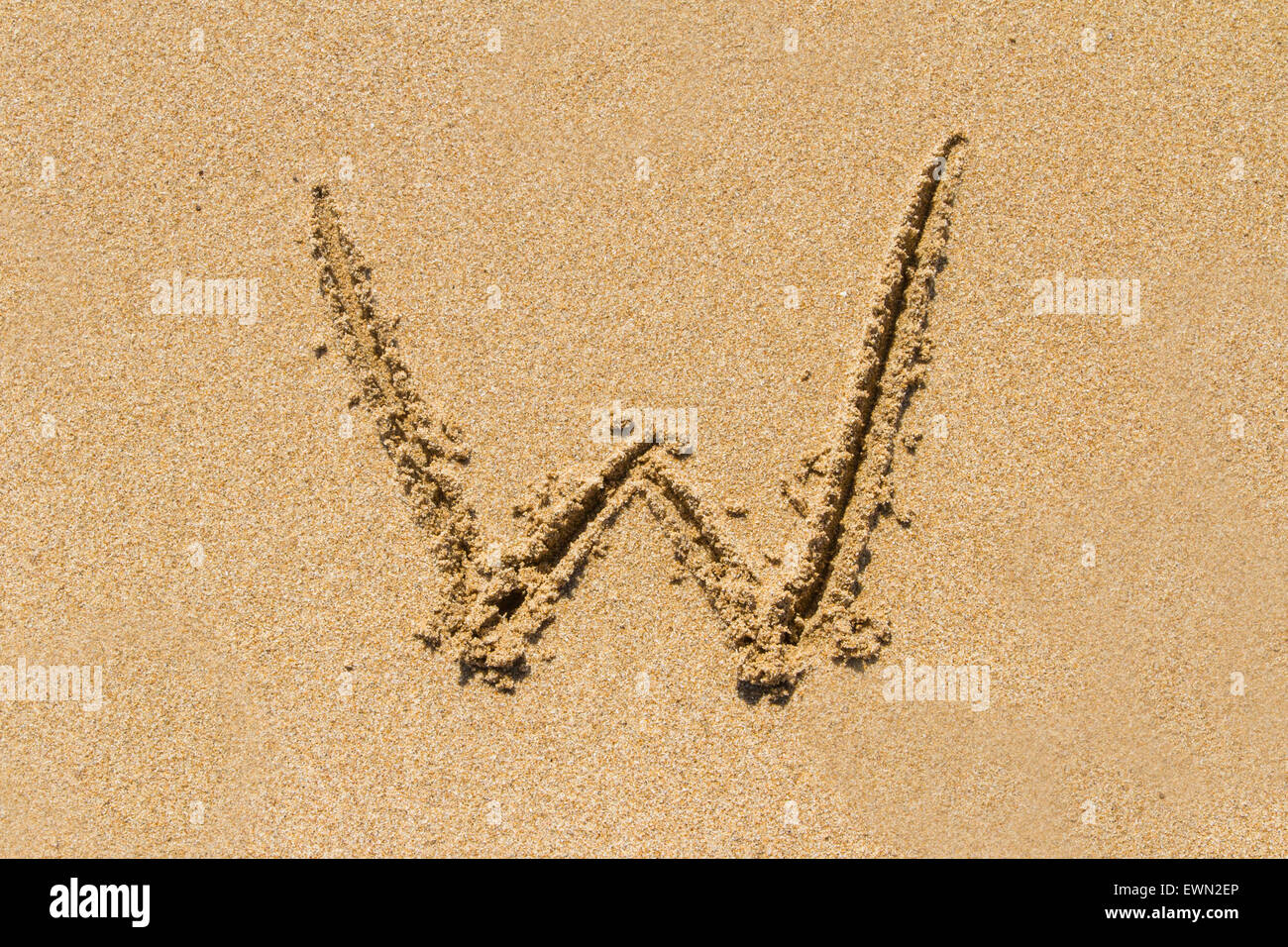 Letter W of the alphabet written on sand with upper case. - Stock Image