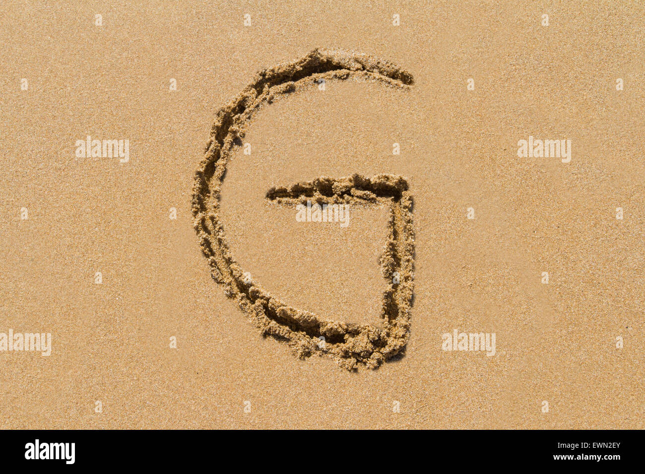 Letter G of the alphabet written on sand with upper case. - Stock Image
