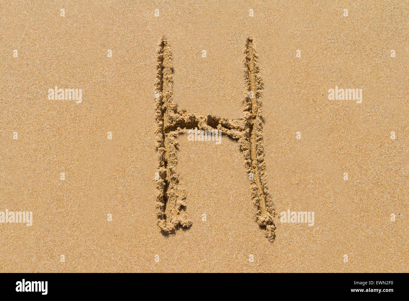 Letter H of the alphabet written on sand with upper case. - Stock Image