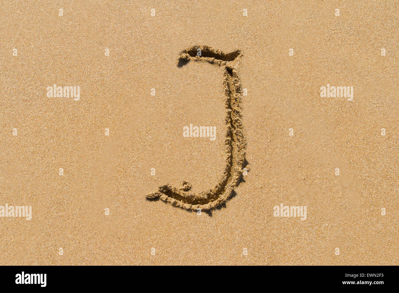 Letter J of the alphabet written on sand with upper case. - Stock Image