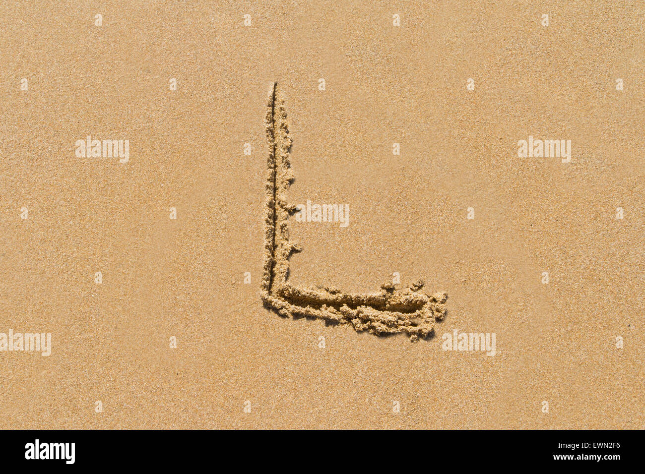 Letter L of the alphabet written on sand with upper case. - Stock Image