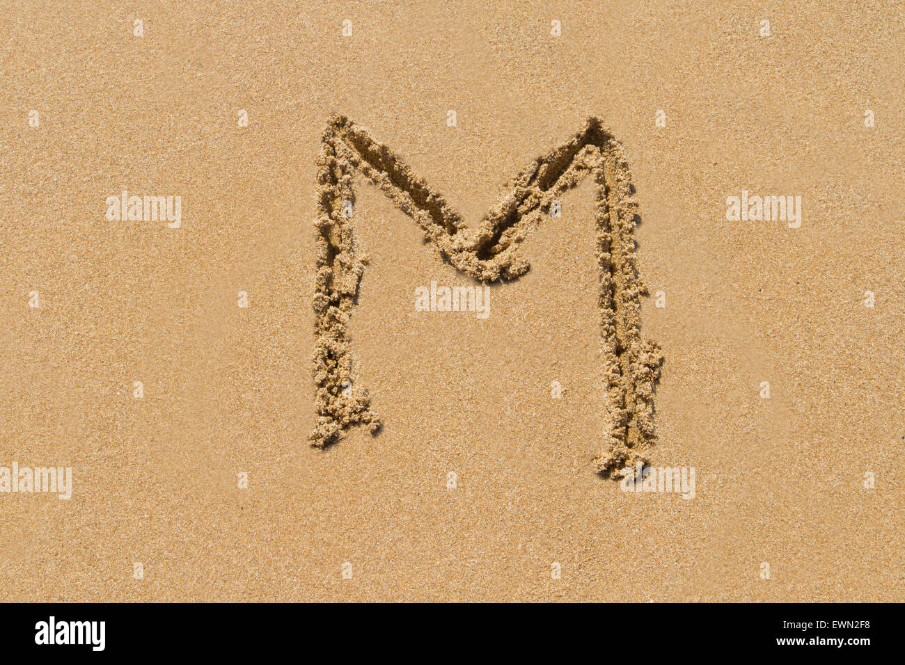 Letter M of the alphabet written on sand with upper case. - Stock Image