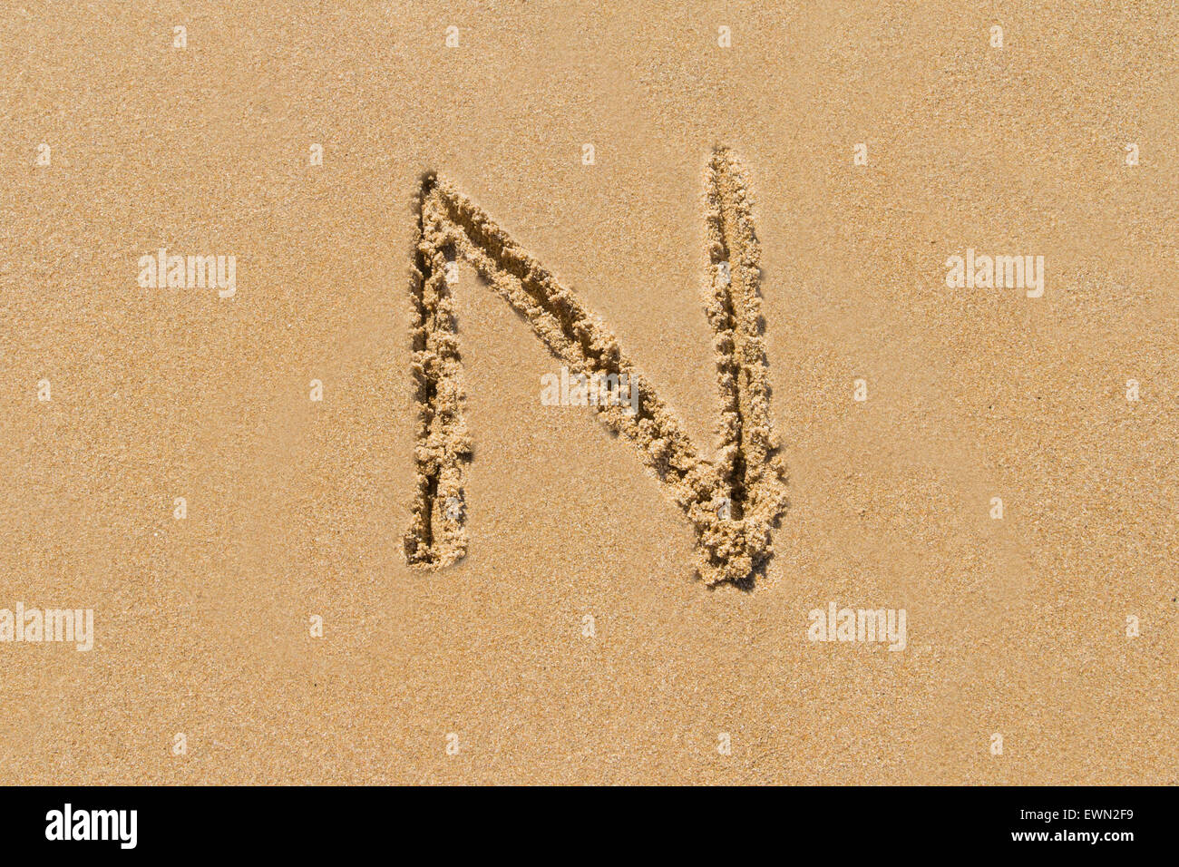 Letter N of the alphabet written on sand with upper case. - Stock Image