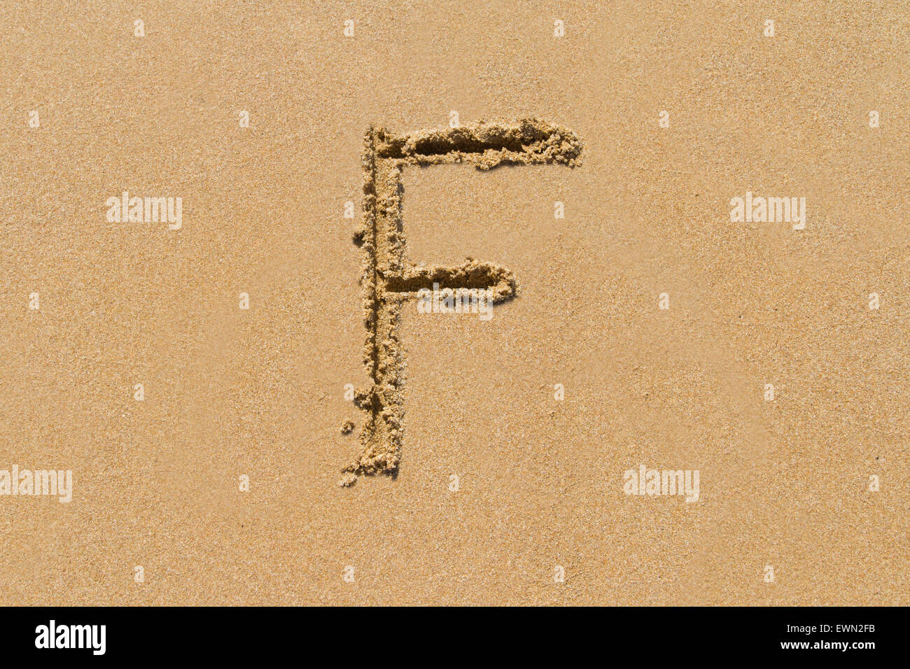 Letter F of the alphabet written on sand with upper case. - Stock Image