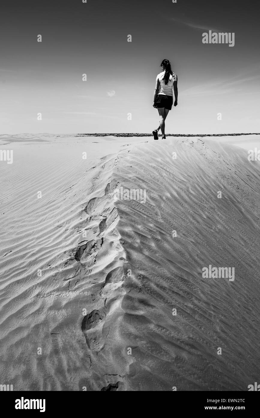 Woman walking on the desert Black and white photo - Stock Image