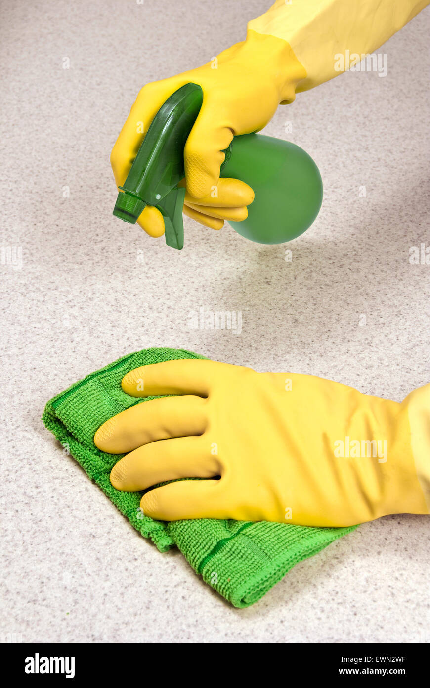 Hands wearing rubber gloves cleaning counter with rag and spray cleaner. - Stock Image