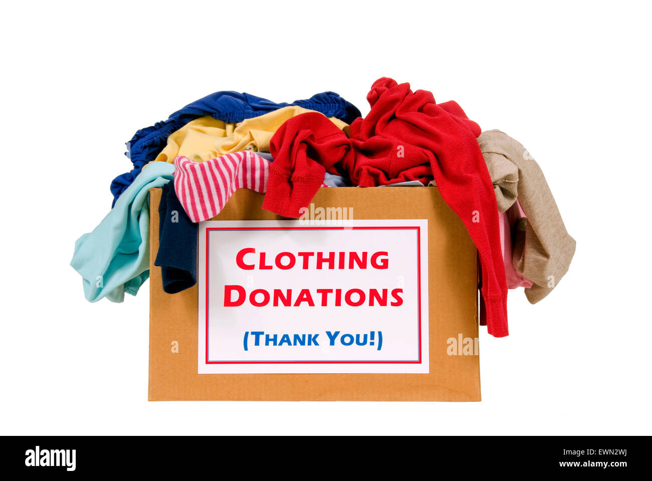 Donation box full of clothes shot in studio isolated on white background. - Stock Image