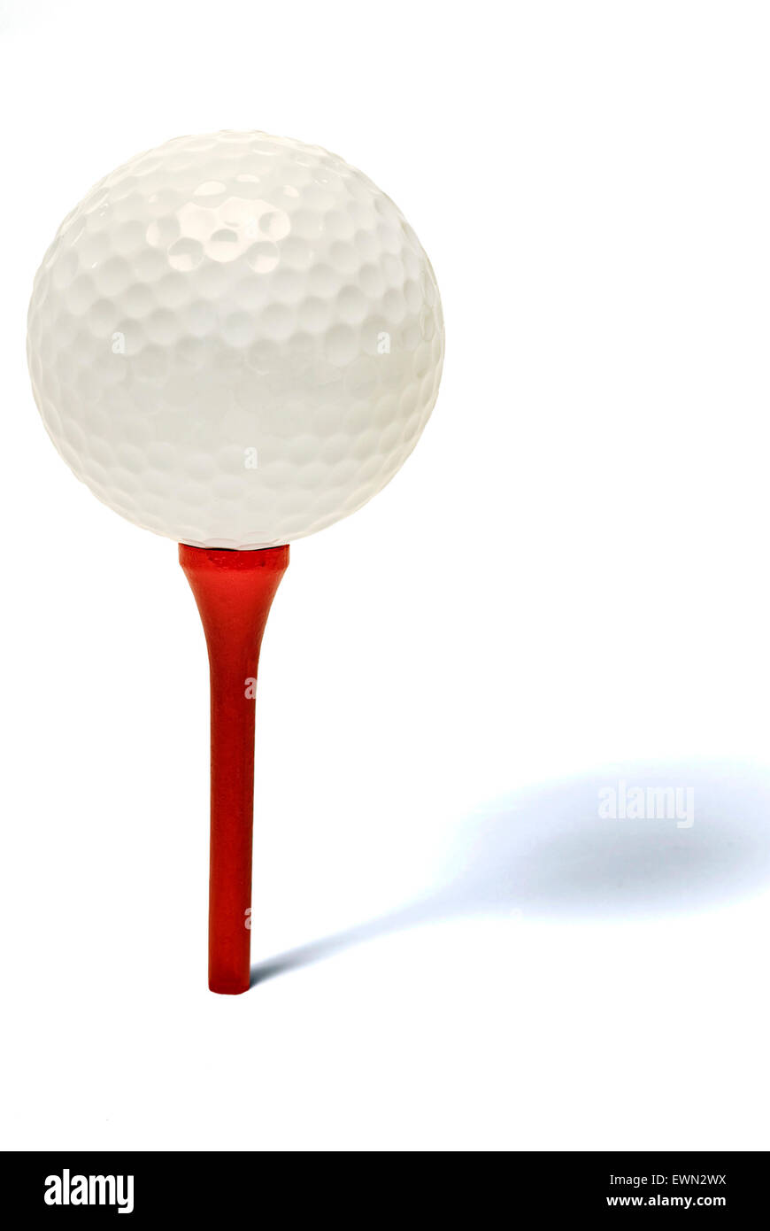 Golf ball on a red wooden tee on white background with a shadow showing depth - Stock Image