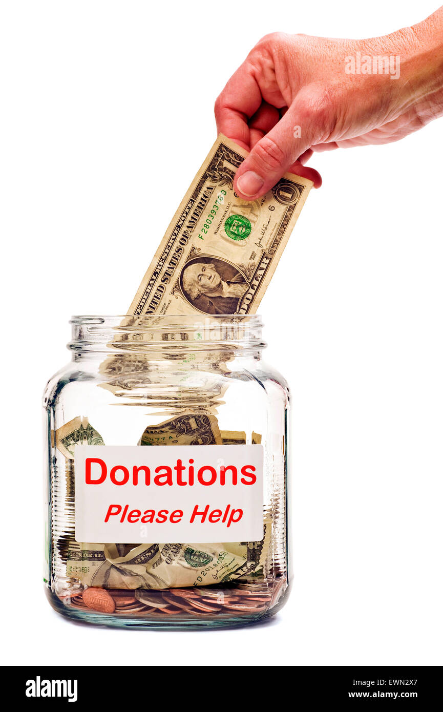Hand putting money into Donation Jar to help people in need.  Isolated on white background - Stock Image