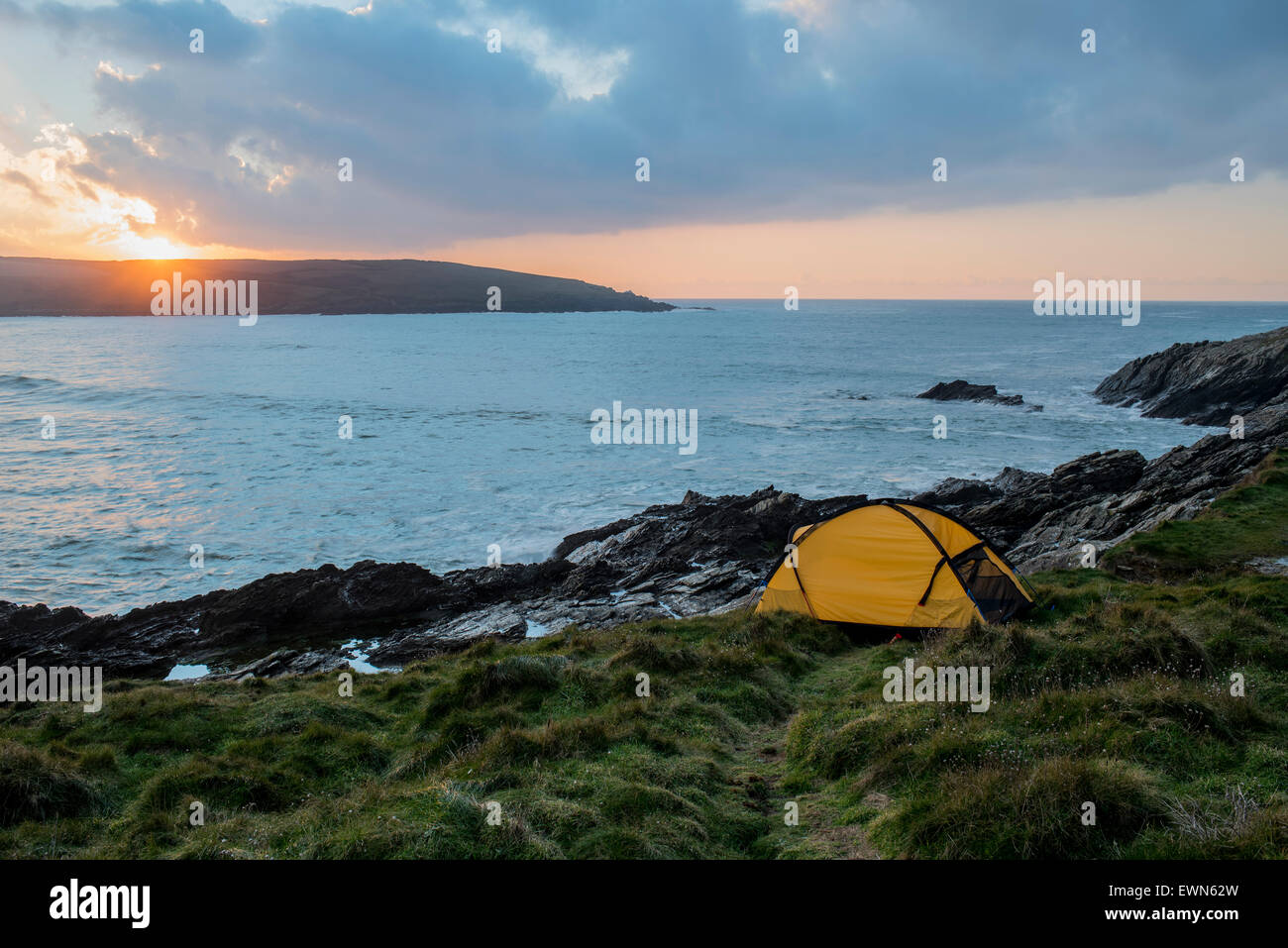 Wild camping by the sea at sunset in Cornwall, UK - Stock Image