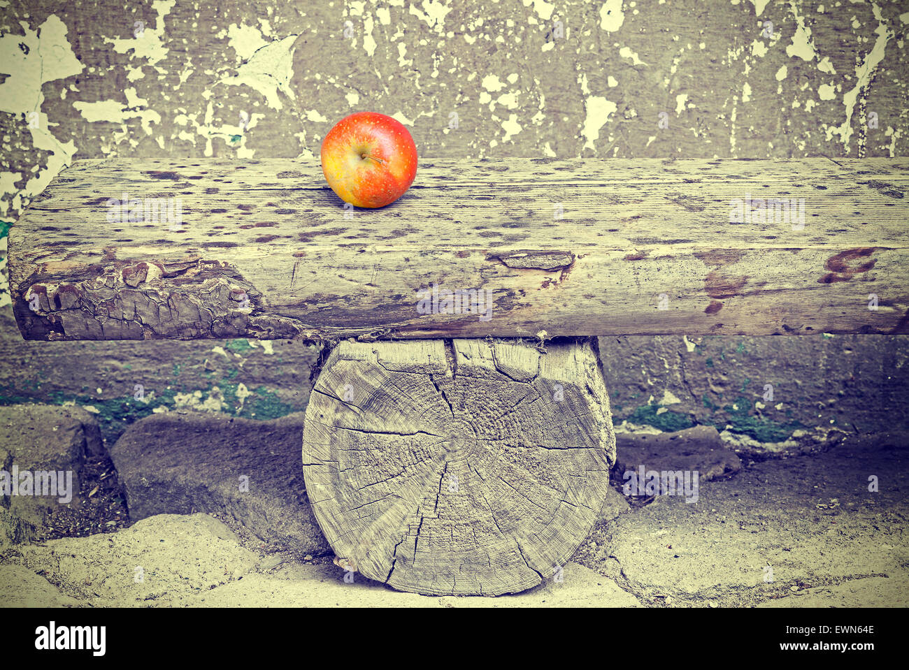 Ripe apple on old wooden bench, retro toned time passing and aging concept. - Stock Image