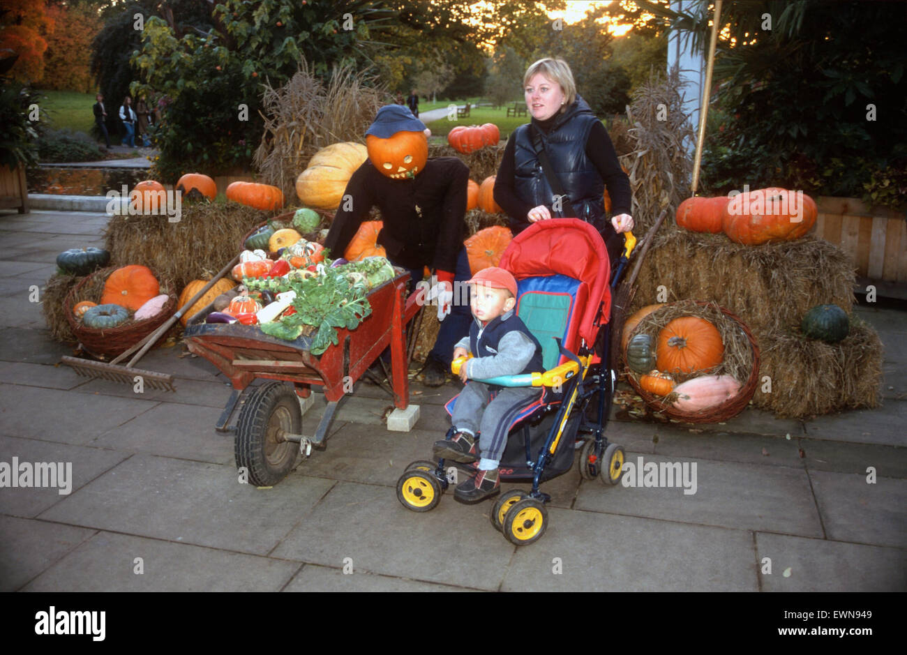 WOMAN WITH CHILD POSES WITH PUMKINS AT KEW GARDENS ENTRANCE - Stock Image