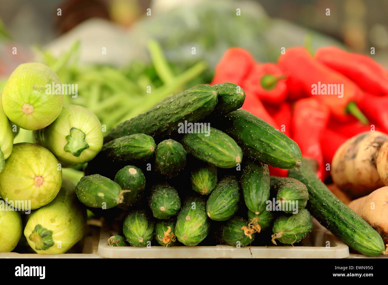 Various vegetables -cucumbers-gherkins-potatoes-red peppers-green beans- market stall in the lower area of town. - Stock Image