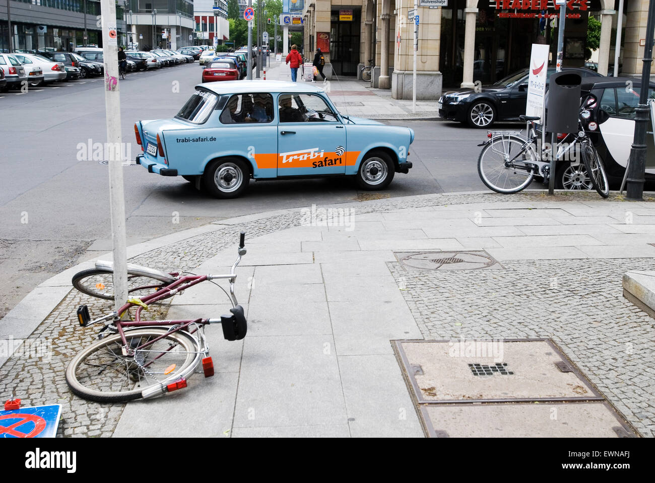 Streetscene with broken bicycle and trabant in Berlin Germany Europe - Stock Image