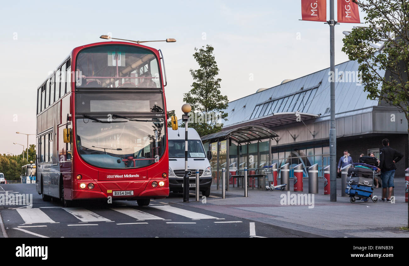 Red double decker National Express West Midlands bus and  airport minibus at a bus stop outside Arrivals, Birmingham - Stock Image