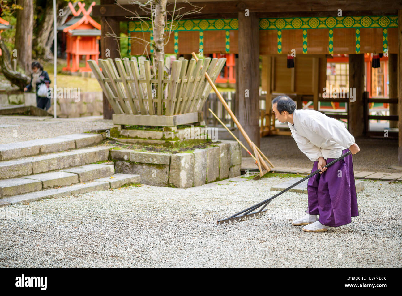 A Shinto Priest rakes a gravel Zen Garden at Kasuga-Taisha Shrine in Nara, Japan. - Stock Image