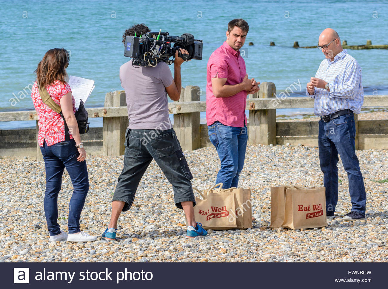 Gregg Wallace and Chris Bavin preparing to be filmed for the 'Eat Well for less?' TV show on a beach by - Stock Image