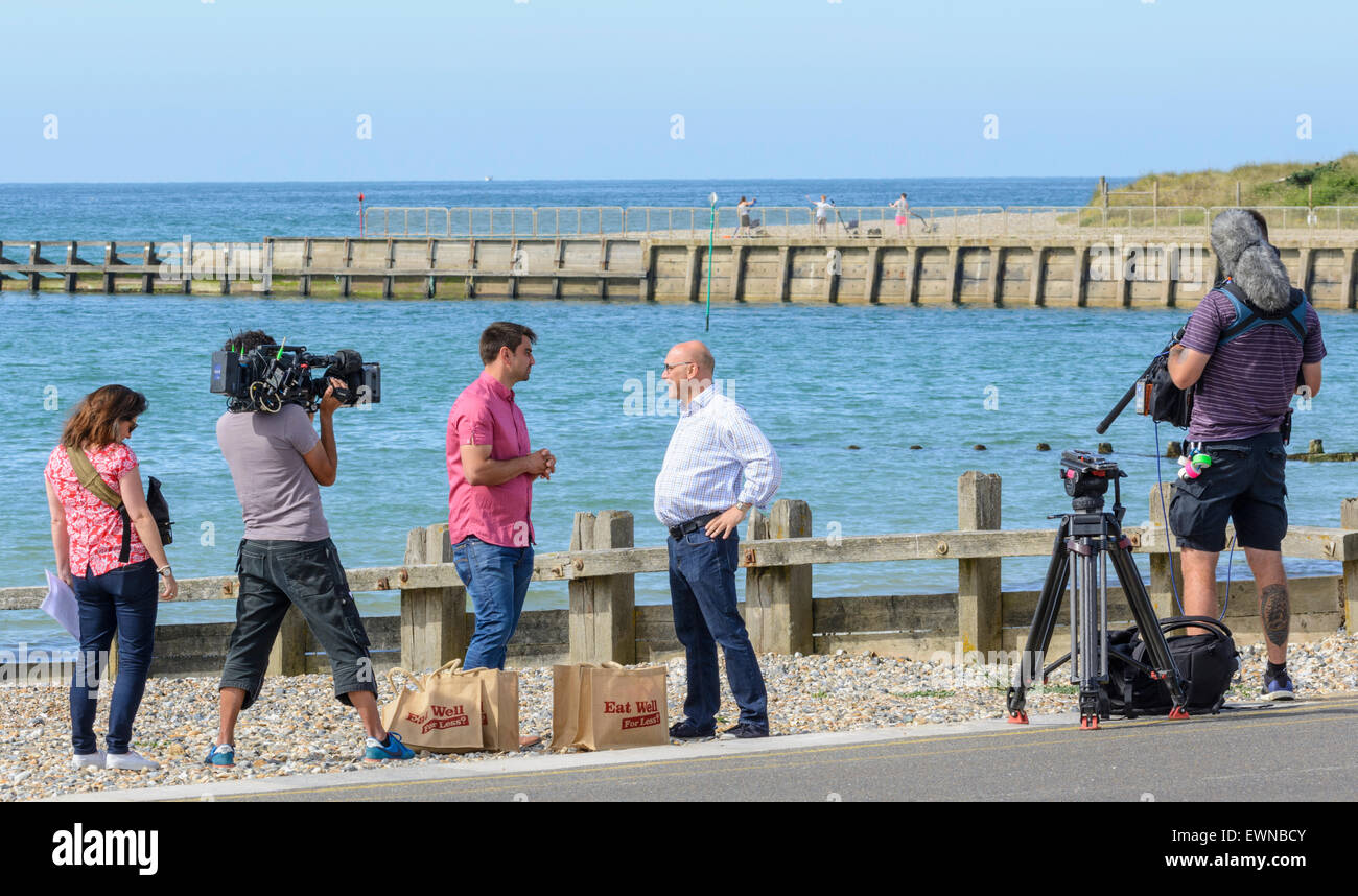 Gregg Wallace and Chris Bavin being filmed for the Eat Well for less TV show on a beach by the sea. - Stock Image