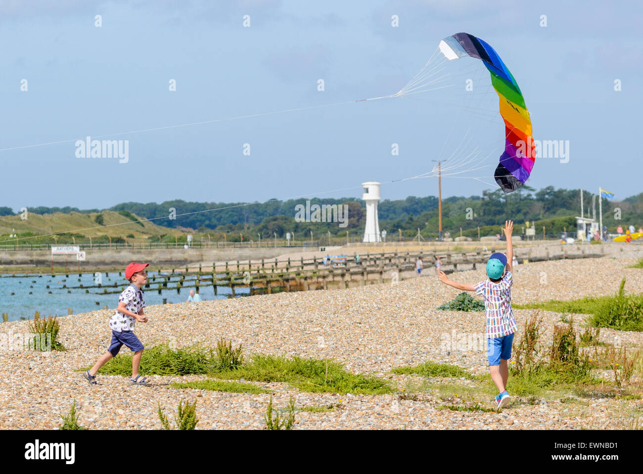 Young boys jumping up to catch a flying kite, on the beach in summer. - Stock Image