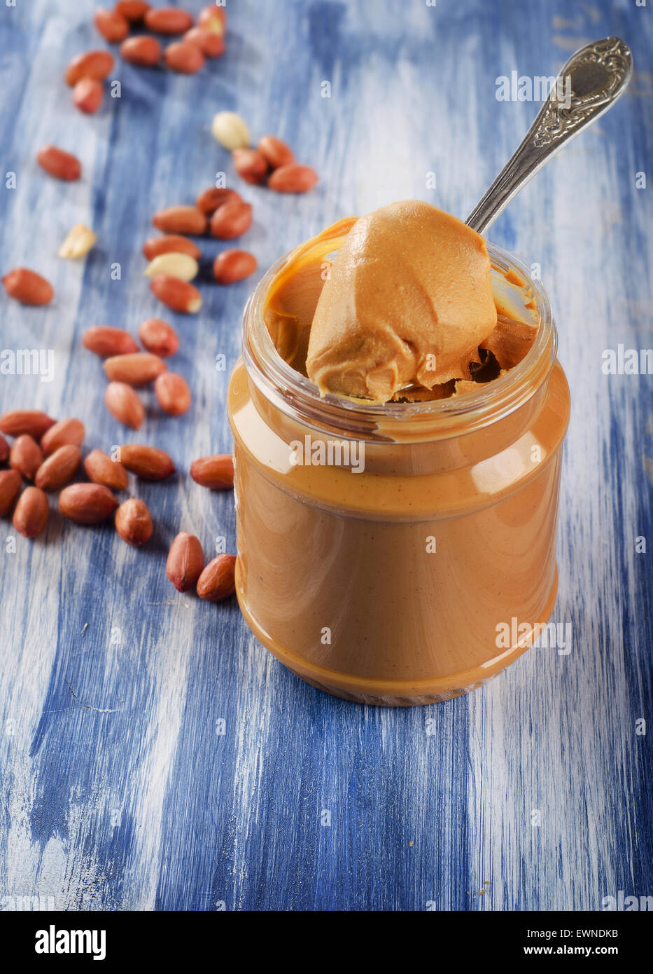 Peanut butter in  jar with peanuts.  Shallow dof. - Stock Image