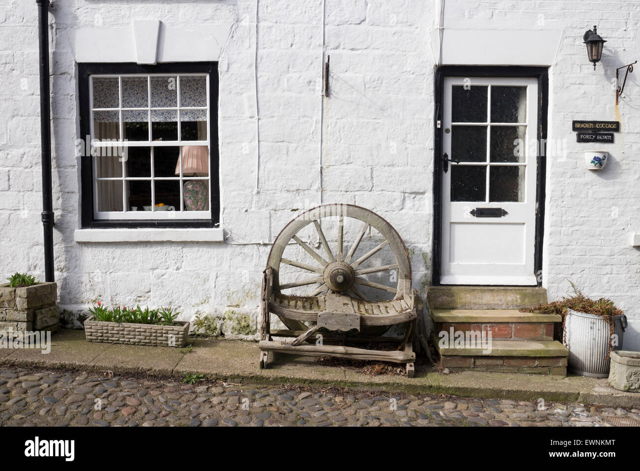 Old wooden cartwheel bench in the foreground, Filey, North Yorkshire - Stock Image