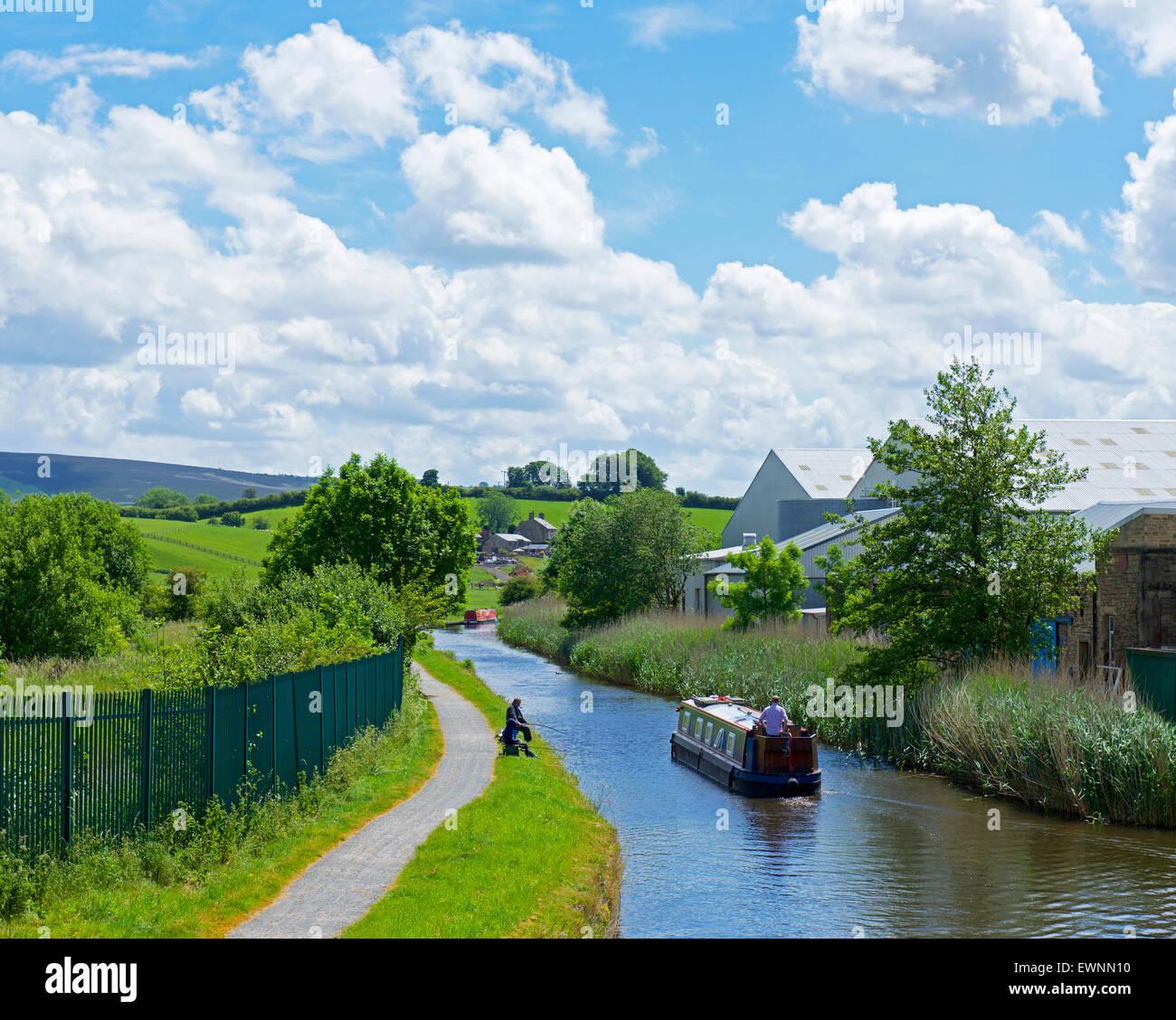Narrowboat and angler on the Leeds and Liverpool Canal near Barnoldswick, Lancashire, England UK - Stock Image