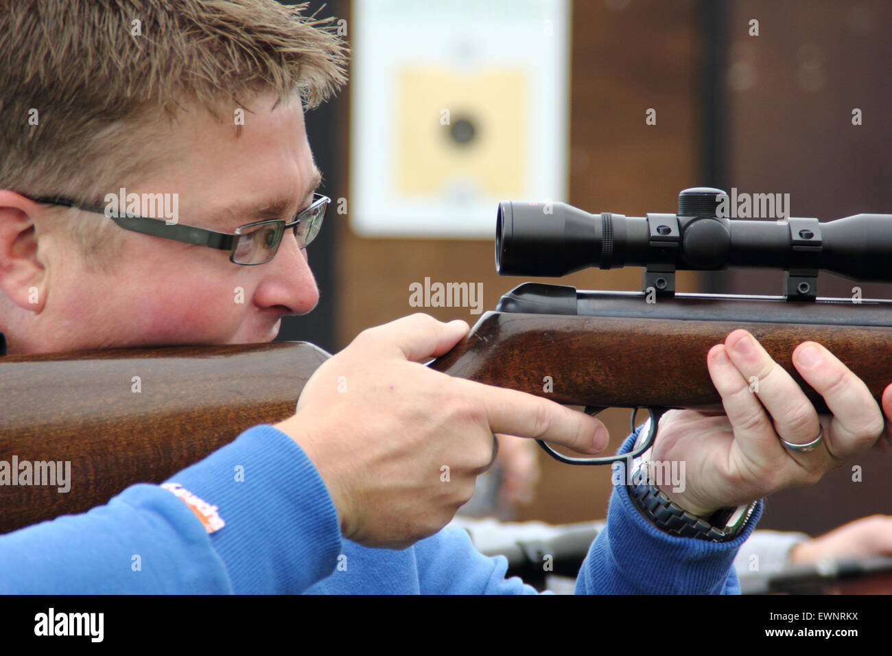 A man takes aim at a target practice stall at an English country fair, Britain UK - Stock Image