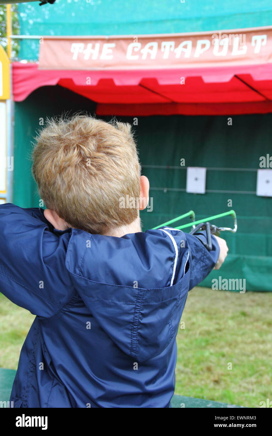 A boy takes aim with a catapult at a country fair in Derbyshire, England UK - Stock Image