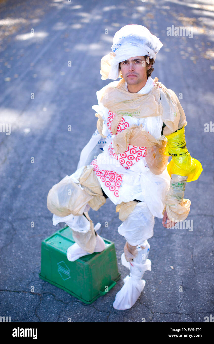 Portrait of adult man dressed in plastic bags with one leg on a recycle bin - Stock Image