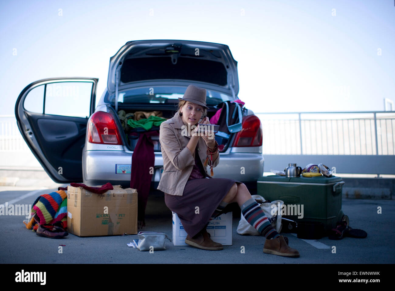 An aspiring actress applies make-up before an audition, while seated amongst her belongings near the trunk of her - Stock Image