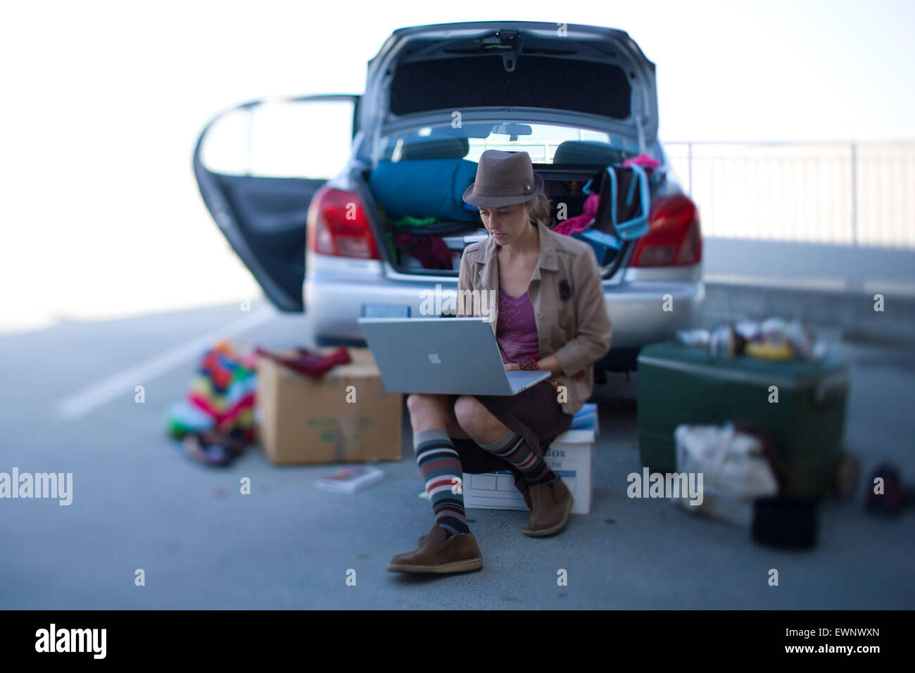 An aspiring actress uses her computer before an audition, while seated amongst her belongings near the trunk of - Stock Image