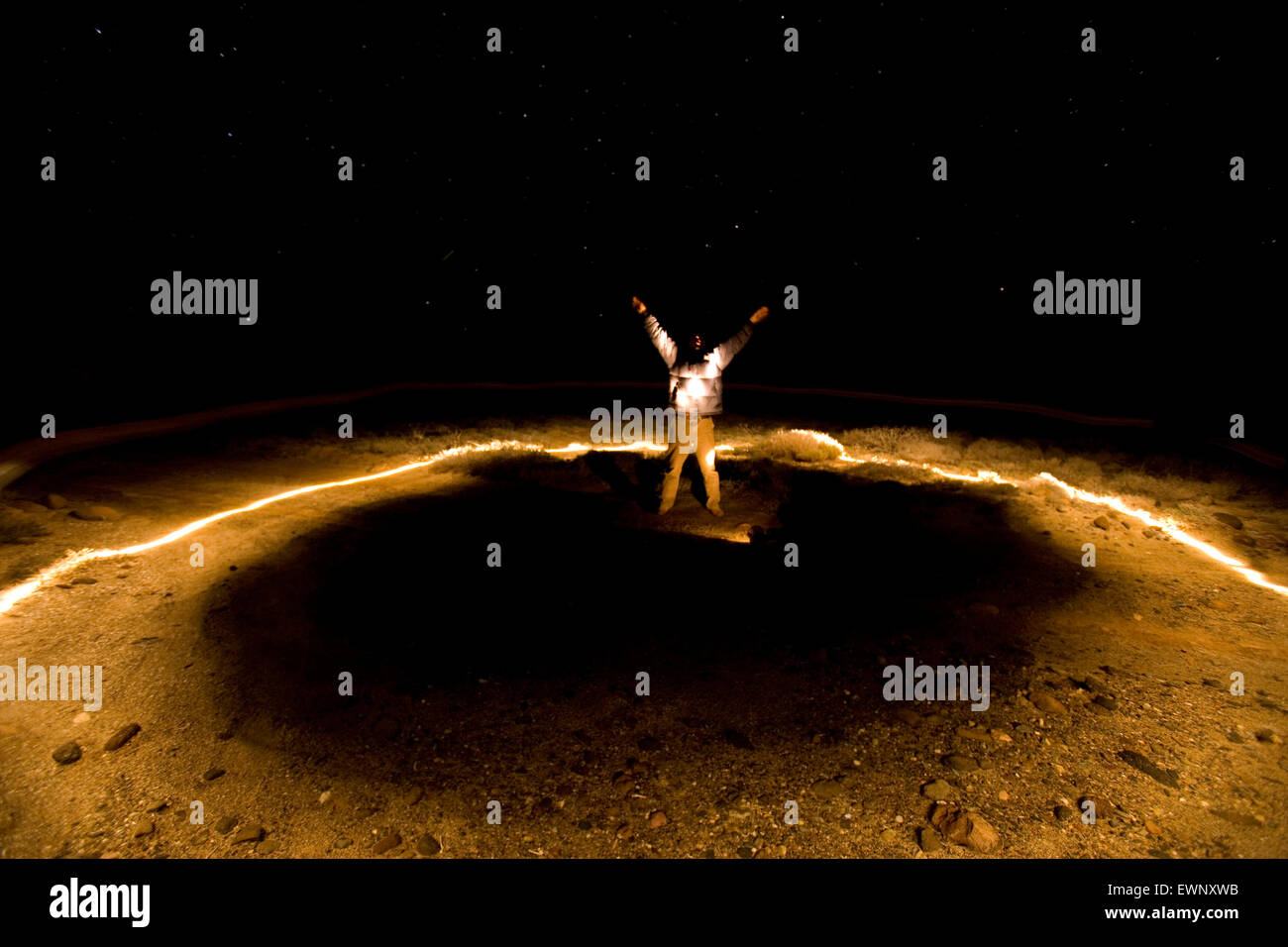 Adult man standing in a circle of light at night - Stock Image