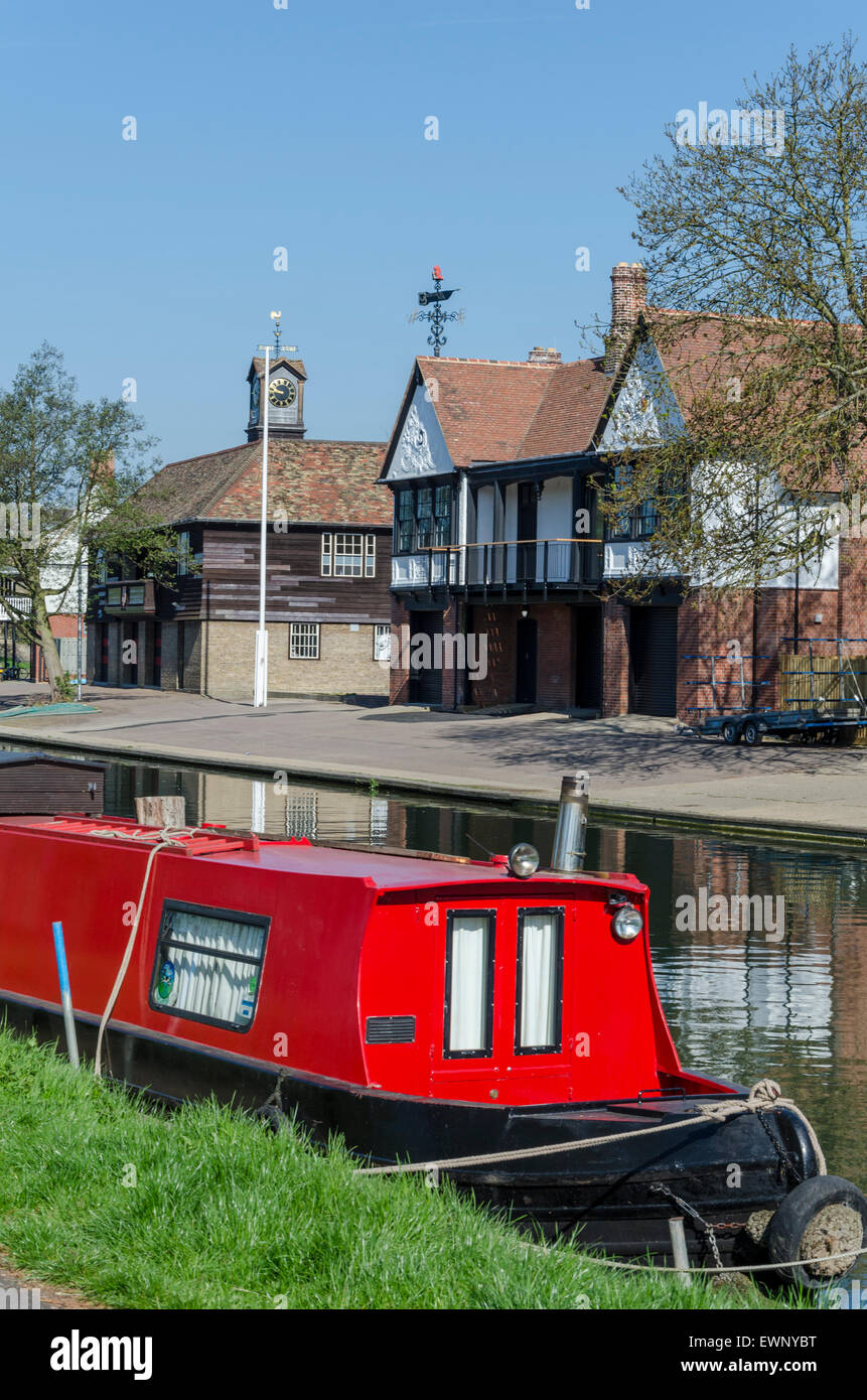 Red narrow boat in front of rowing club buildings on the River Cam, Cambridge, UK - Stock Image