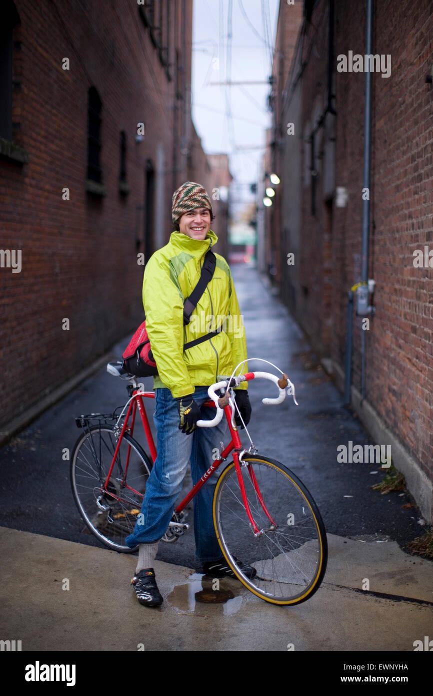 Portrait of a bike commuter on a rainy street - Stock Image